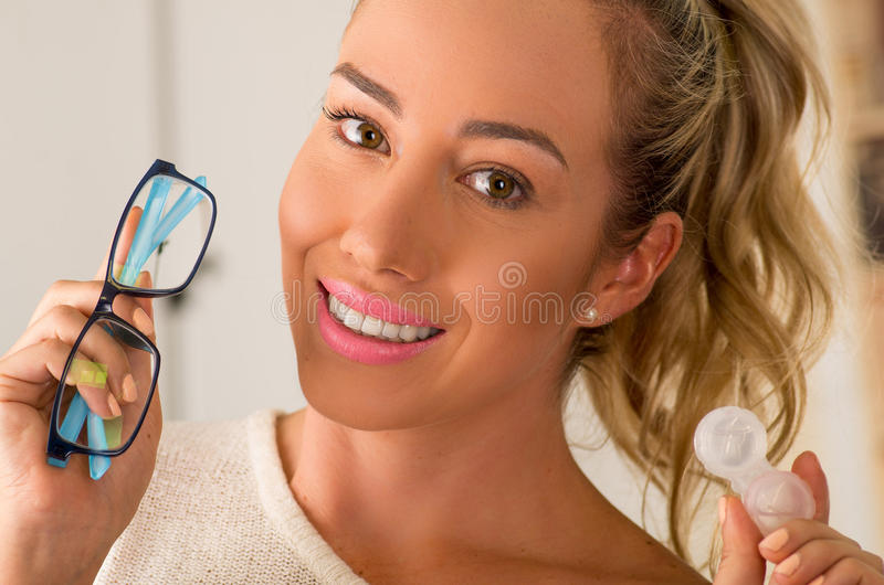 Smiling young blonde woman holding contact lens case on hand and holding in her other hand a blue glasses on blurred stock photography