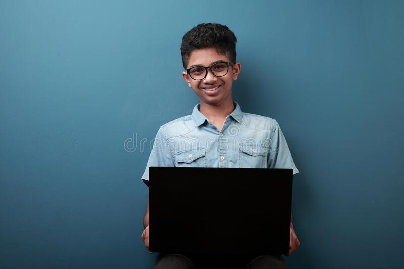 Smiling young boy with laptop stock images