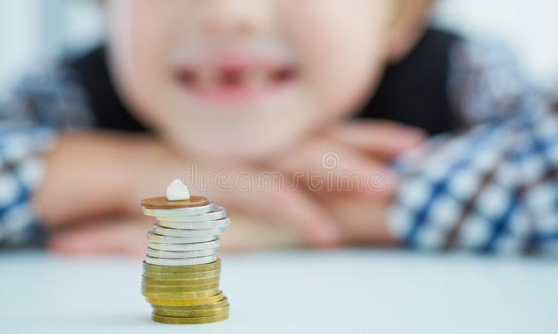 Smiling young boy with missing front tooth. Pile of coins with a baby tooth on top. Tooth fairy giving money coins as a reward for child teeth stock image