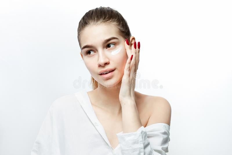 Smiling young brown-haired girl without makeup dressed in white clothes puts a cream on her face on the white background stock images