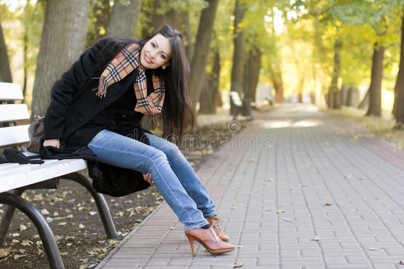 Smiling young brunette. Sitting on a bench in autumn park royalty free stock photo