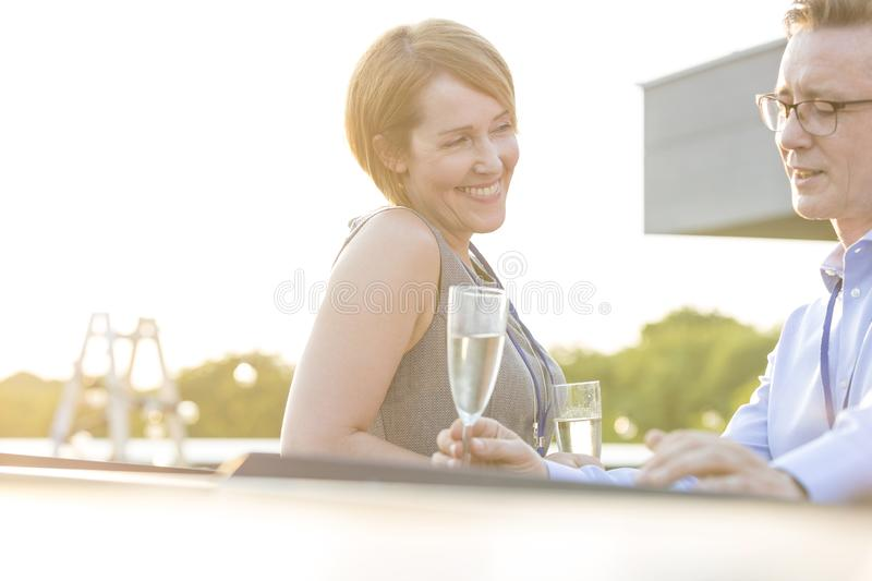 Smiling young business colleagues sitting with wineglasses at success party on rooftop royalty free stock photos