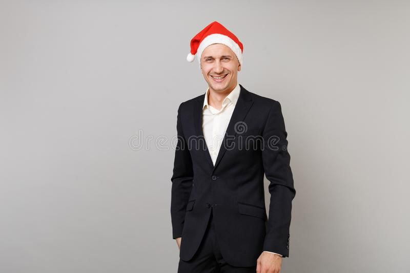Smiling young business man in classic black suit, Christmas hat isolated on grey wall background in studio. Achievement stock images