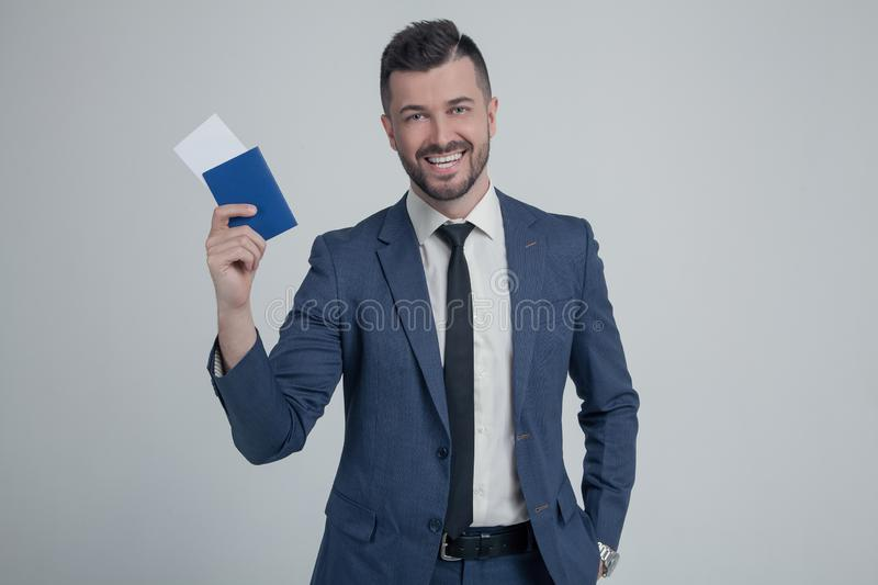 Smiling young business man in classic black suit, shirt hold passport, boarding pass ticket isolated on grey wall background in royalty free stock photography