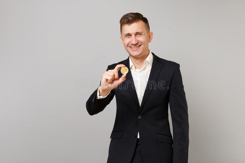 Smiling young business man in classic black suit and shirt holding bitcoin, future currency isolated on grey wall stock image