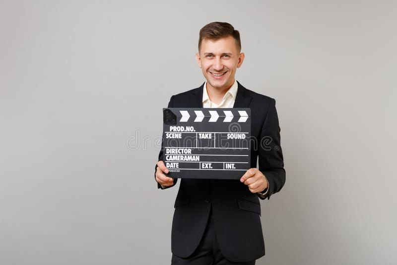 Smiling young business man in classic black suit, shirt holding classic black film making clapperboard isolated on grey royalty free stock photography
