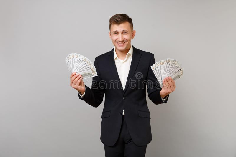 Smiling young business man in classic black suit, shirt holding lots bunch of dollars banknotes, cash money isolated on royalty free stock image