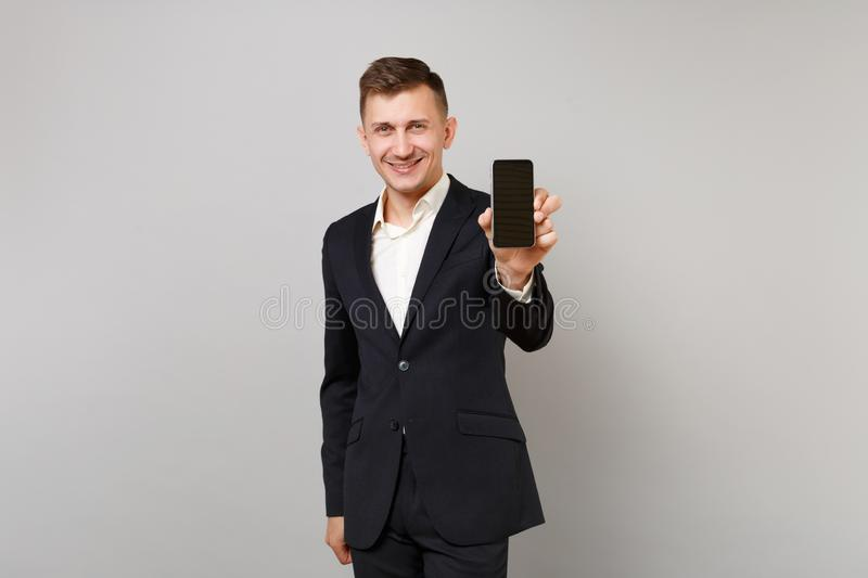 Smiling young business man in classic black suit, shirt holding mobile phone with blank empty screen isolated on grey stock photo