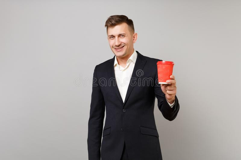 Smiling young business man in classic black suit, shirt holding paper cup with coffee or tea isolated on grey wall royalty free stock photography