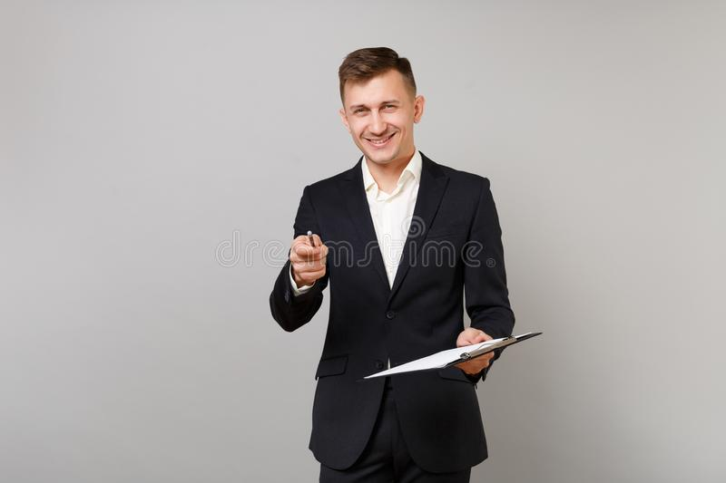 Smiling young business man in classic suit pointing pencil on camera holding clipboard with papers document isolated on stock image