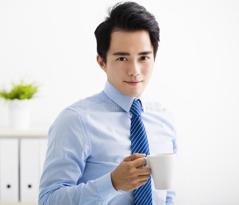 Smiling young business man drinking coffee royalty free stock image