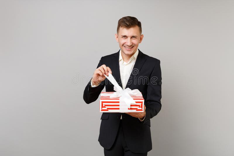 Smiling young business man in suit opening red striped present box with gift ribbon isolated on grey background royalty free stock images