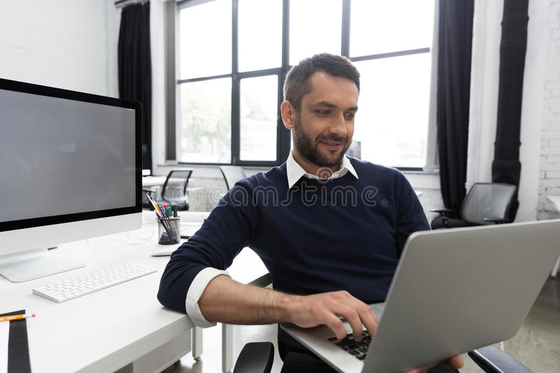 Smiling young business man using laptop stock images