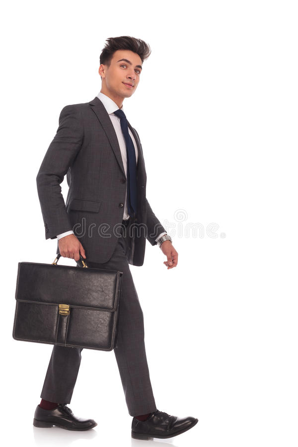 Smiling young business man walking forward and looking up royalty free stock photos