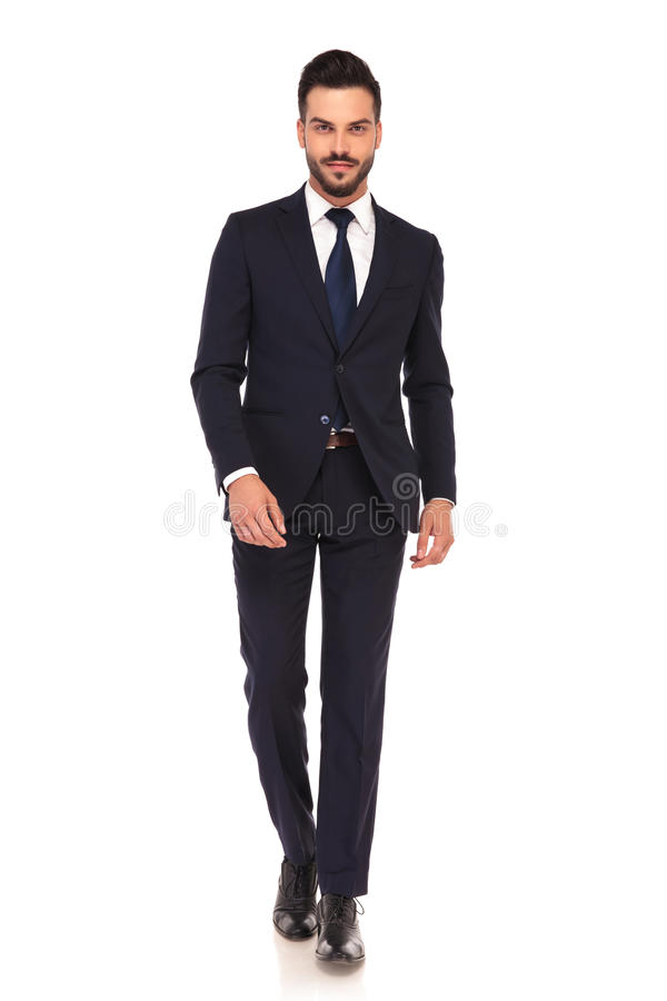 Smiling young business man is walking forward. On white background royalty free stock image