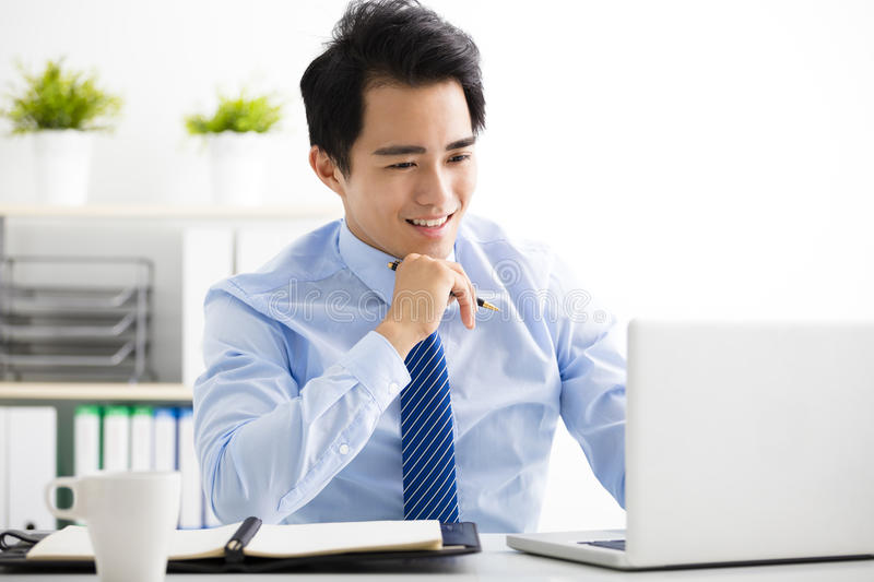 Smiling young business man working on laptop royalty free stock images