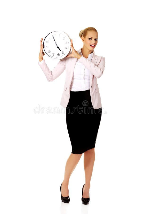 Smiling young business woman holding office clock stock photo