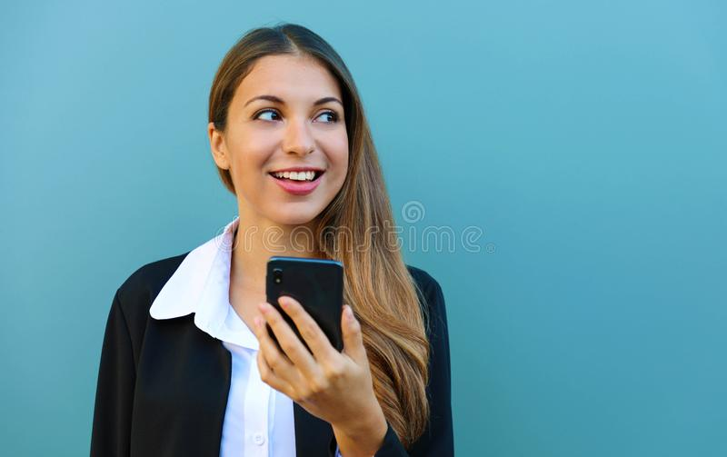 Smiling young business woman looking to the side against blue background. Copy space stock image