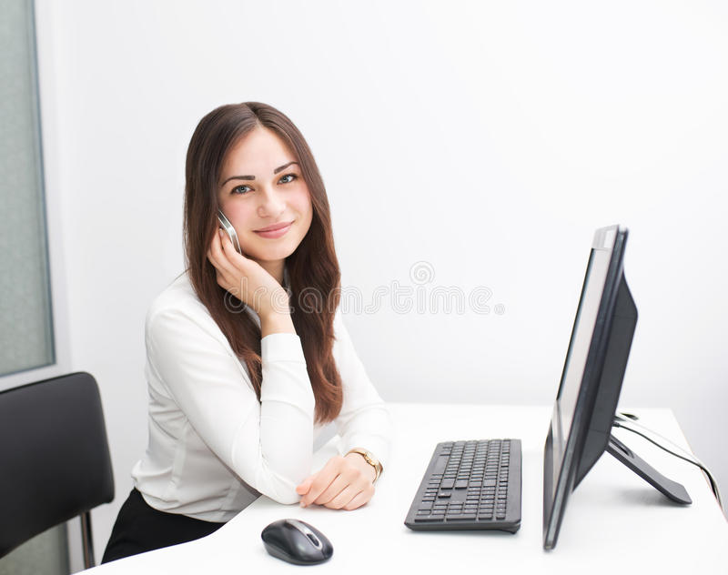Smiling young business woman speaks on the phone at work stock images