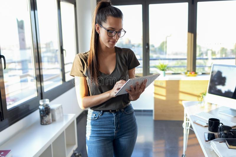 Smiling young business woman using her digital tablet while standing next to the window in the office stock photos