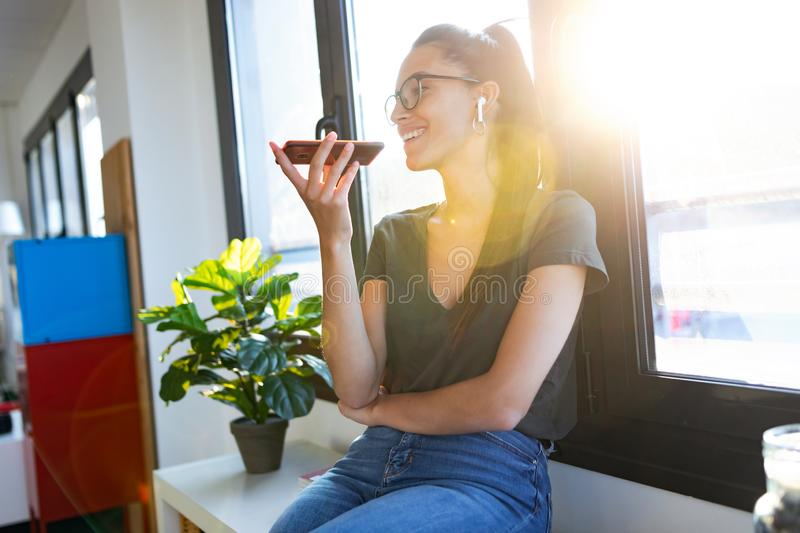 Smiling young business woman using her free hands to make a call with mobile phone in the office royalty free stock images