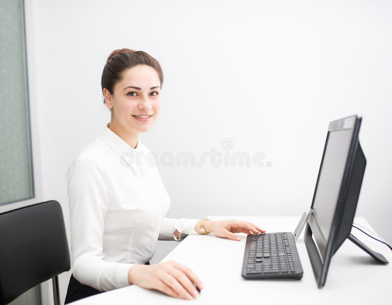 Smiling young business woman working in the office royalty free stock photography