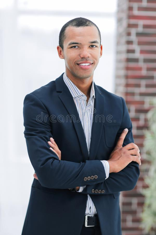 Smiling young businessman on background of office royalty free stock image