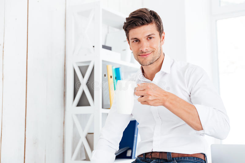 Smiling young businessman drinking cup of tea in the office. Smiling young businessman drinking cup of tea at lunch break in the office royalty free stock photography