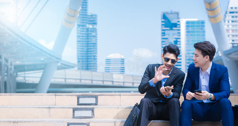 Smiling young businessman enjoying a positive conversation talking with a mature business partner in a modern space in city stock photo