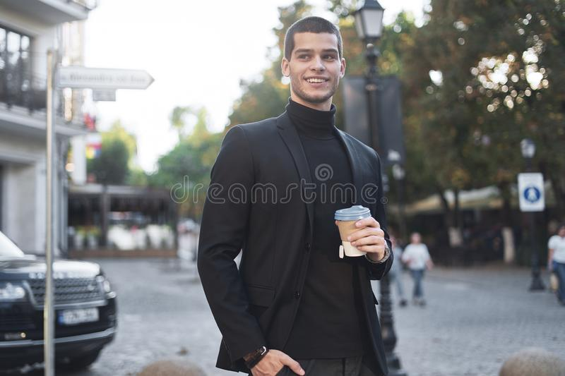Smiling young businessman going to the work with coffee royalty free stock images