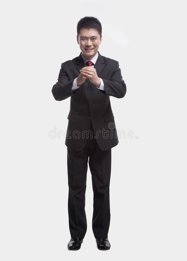 Smiling young businessman with hands clasped together bowing toward camera, studio shot stock photo