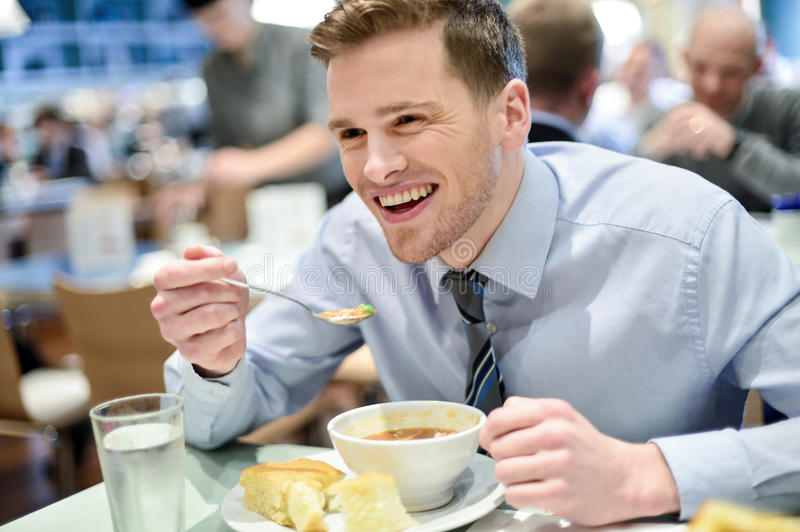 Smiling young businessman having lunch stock photo