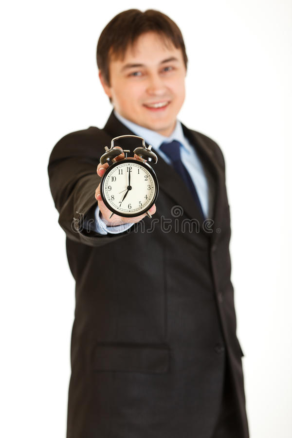 Smiling young businessman holding alarm clock royalty free stock image