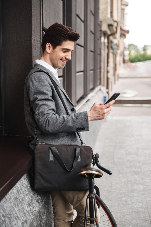 Smiling young businessman leaning on a wall stock photos