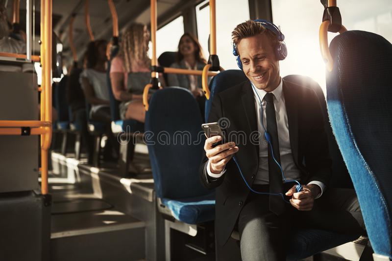 Smiling young businessman listening to music on his morning comm. Smiling young businessman wearing a suit sitting on a bus during his morning commute listening stock photography