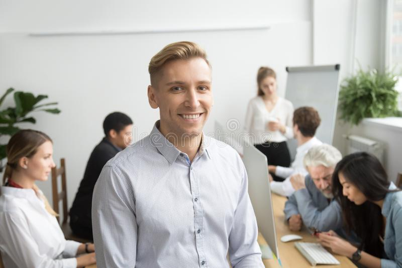 Smiling young businessman looking at camera, office people at ba stock image