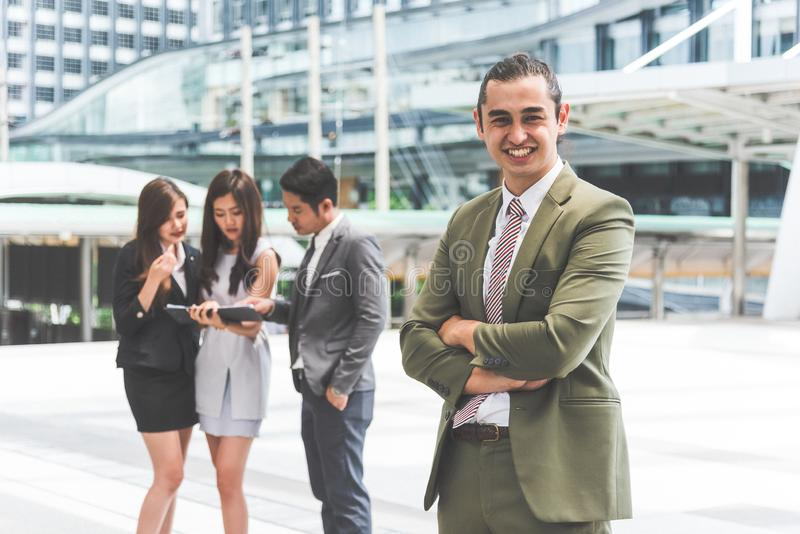 Smiling young businessman looking into camera with his arms crossed and teammates background in urban. Modern business office team stock photo