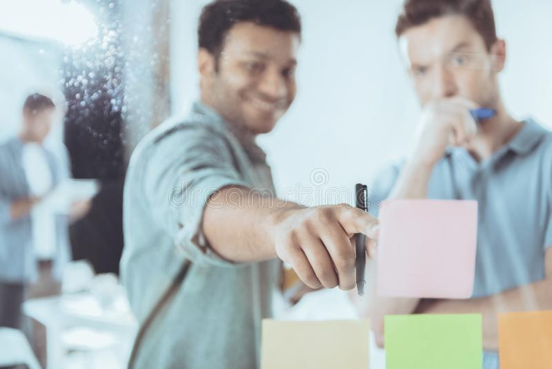 smiling young businessman pointing at sticky note to focused colleague stock photo