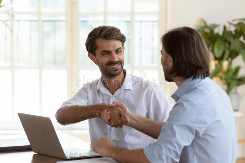 Smiling young businessman shaking hands with confident male coworker. royalty free stock image