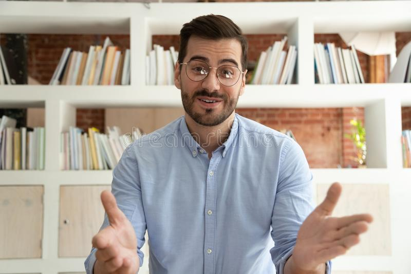 Young businessman talk on webcam having video call. Smiling young businessman sit at desk talk on webcam having video call or conversation with client, motivated royalty free stock photography