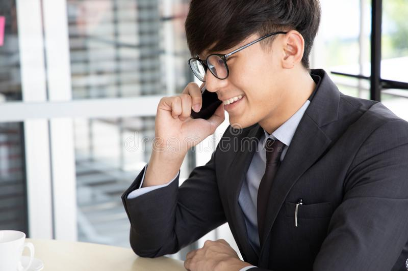 Smiling young businessman  talking on his smartphone while he working , sitting in his office at desk wearing a black suit royalty free stock images