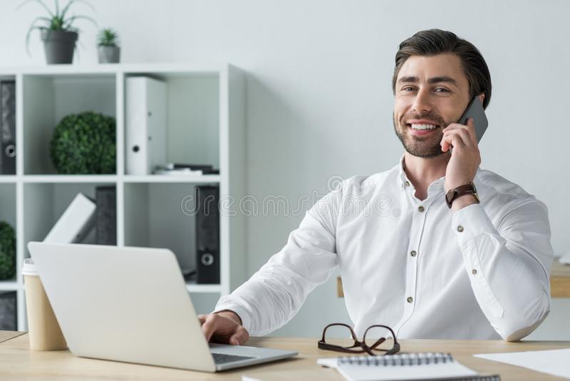 smiling young businessman talking by phone at workplace and looking stock photo