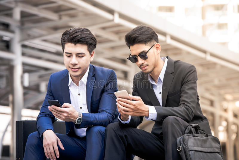 Smiling young businessman use smartphone conversation talking with a mature business partner royalty free stock images