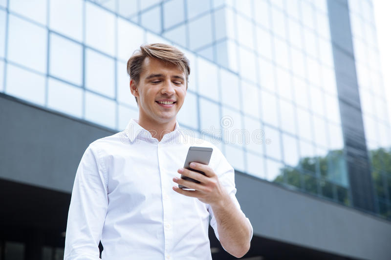 Smiling young businessman using mobile phone near business center stock images