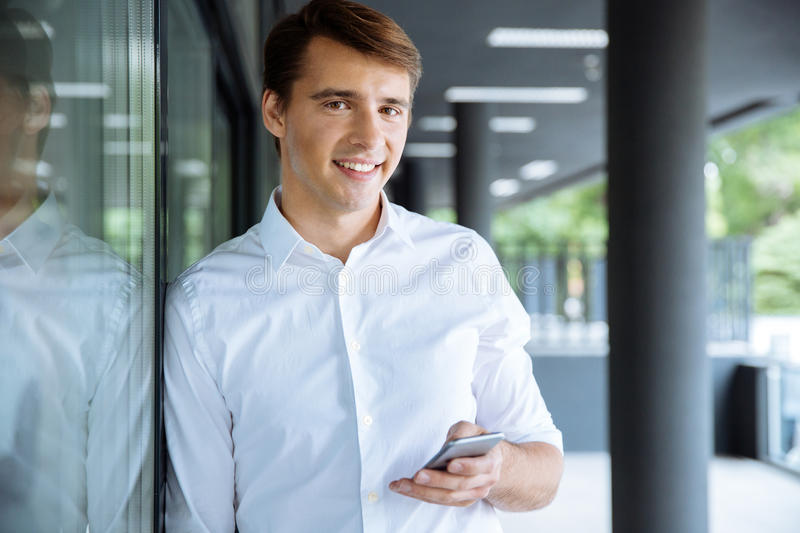 Smiling young businessman using smartphone royalty free stock photography