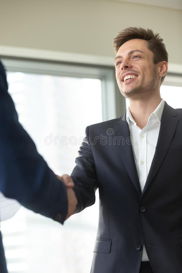 Smiling young businessman wearing black suit shaking male hand,. Smiling young businessman wearing suit shaking male hand, greeting welcoming handshake at stock image
