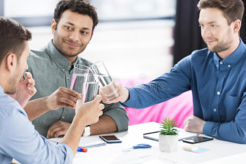 Smiling young businessmen drinking water and discussing new project. Business teamwork concept stock photo