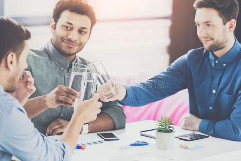 Smiling young businessmen drinking water and discussing new project business. Teamwork concept stock photos