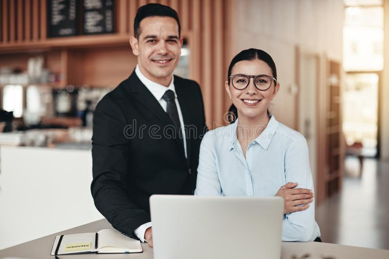 Smiling young businesspeople working together in a modern office royalty free stock photos