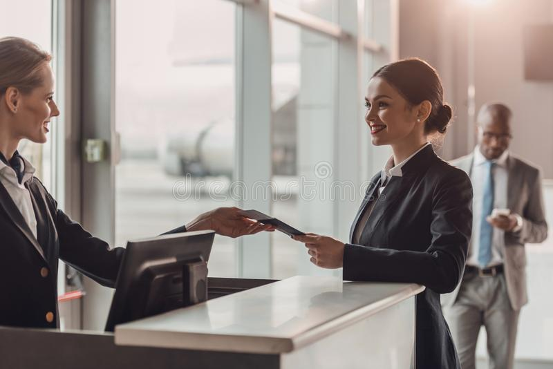 smiling young businesswoman giving passport and ticket to staff at airport check royalty free stock photo